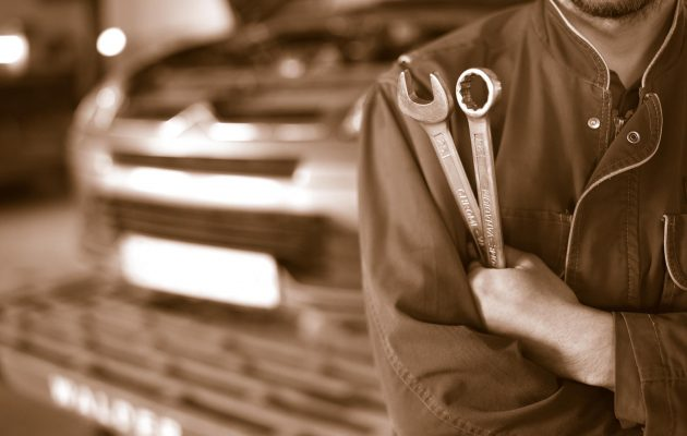 sepia car mechanic technician holding wrenches