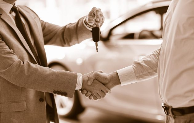 sepia people shaking hands car buying key